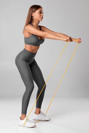 Donna fitness che utilizza una fascia di resistenza nella sua routine di esercizi. Allenamento atletico sexy della ragazza con l'espansore su fondo grigio