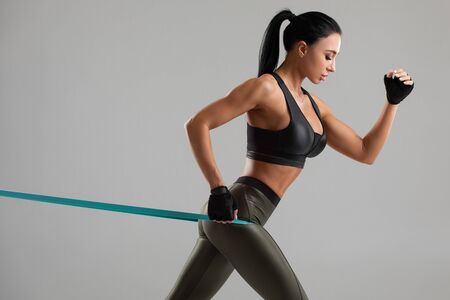 Fitness woman using a resistance band in her exercise. Sexy athletic girl workout with expander on grey background