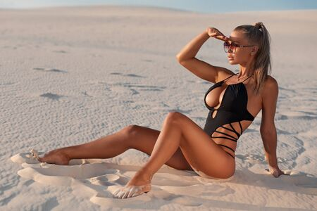 Sexy woman in swimsuit enjoying summer sun and tanning on the beach Standard-Bild