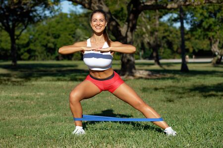 Athletic woman workout with resistance band outdoors. Fitness girl doing exercise for legs at the park