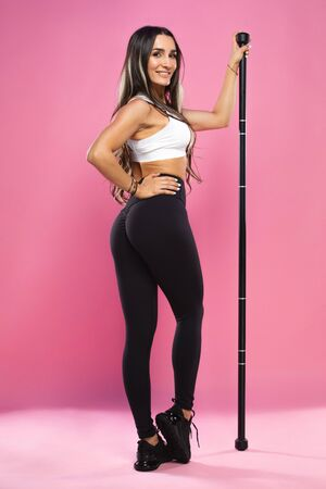 Fitness woman workout on pink background. Athletic gril with body bar