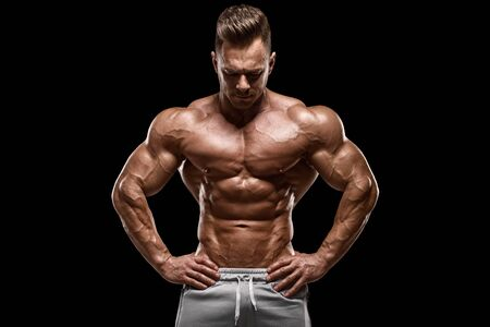Muscular man showing muscles isolated on the black background. Strong male naked torso abs 写真素材