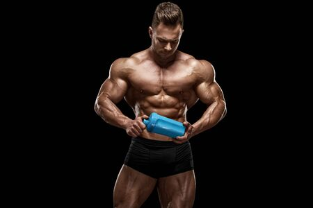 Muscular man with shaker isolated on black background, shaped abdominal. Strong male naked torso abs, workout