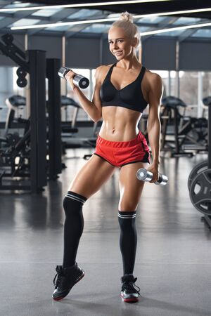Beautiful fitness woman workout in gym. Smiling athletic girl doing exercise for biceps 写真素材