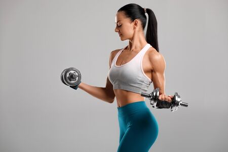 Fitness woman doing exercise for biceps on gray background. Muscular woman workout with dumbbells 写真素材