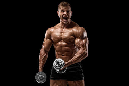 Muscular man with dumbbells working out isolated on black background. Strong male torso abs Stock Photo