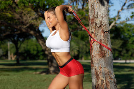 Athletic woman workout with resistance band outdoors. Fitness girl doing exercise for triceps at the park