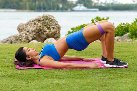 Fitness woman doing glute bridge exercise with resistance band, outdoors. Athletic girl workout