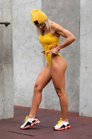 Athletic woman showing muscular legs. Fitness girl with shaped butt outdoors