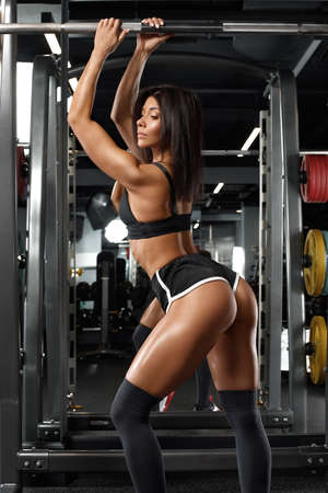 Athletic woman with beautiful butt in gym. Fitness girl with shaped booty
