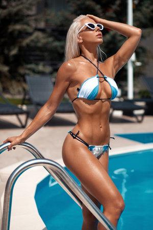 Sexy woman in bikini enjoying summer sun and tanning during holidays in pool. Beautiful girl in swimsuit Standard-Bild