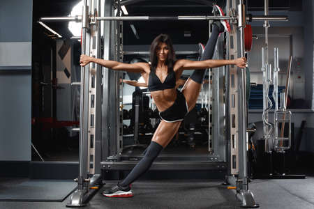 Fitness woman doing a twine in gym. Athletic girl doing stretching exercise