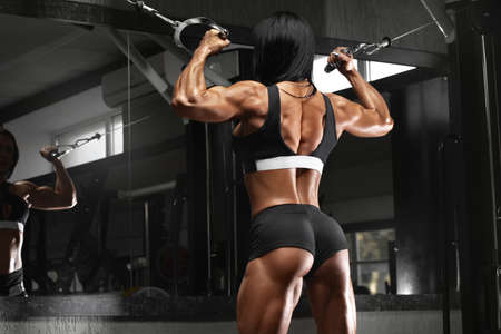 Muscular woman in gym showing back muscles. Strong fitness girl working out Standard-Bild