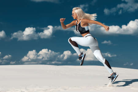 Fitness woman jumping and running on sky background. Athletic girl working out