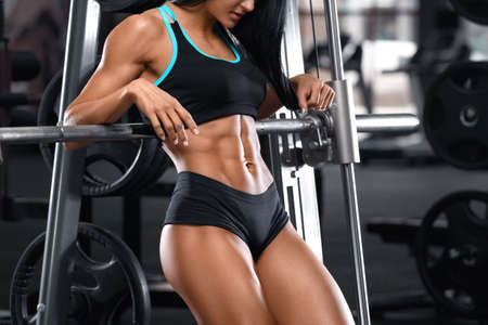Fitness woman showing abs and flat belly in gym. Beautiful athletic girl, shaped abdominal Standard-Bild