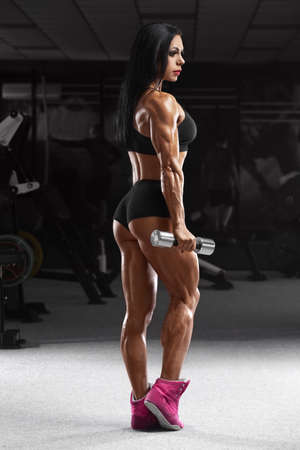 Muscular woman in gym working out. Strong fitness girl