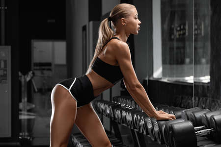 Sexy athletic girl workout in gym. Fitness woman doing exercise. Beautiful butt in leggings