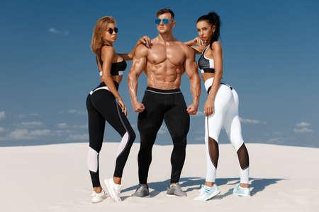 Sporty fitness models in sportswear. Athletic man and women in leggings outdoor Standard-Bild