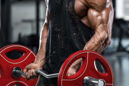 Muscular man in gym doing exercises for biceps, working out. Strong bodybuilder male