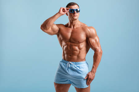 Handsome muscular man  torso abs, isolated on blue background. Fitness male model in fashionable sunglasses