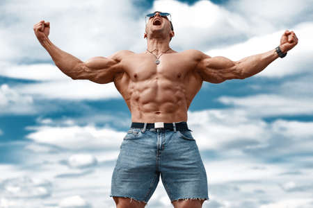 Muscular man showing muscles on sky background. Strong male  torso abs