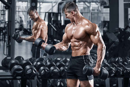 Muscular man working out in gym. Strong male naked  abs Standard-Bild