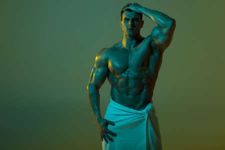 Sexy muscular man with towel. Strong male  torso abs Standard-Bild