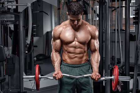 Muscular man working out in gym. Strong male  torso abs
