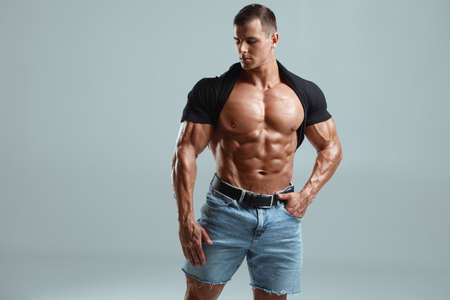 Muscular man fitness model isolated on background. Strong male naked torso abs