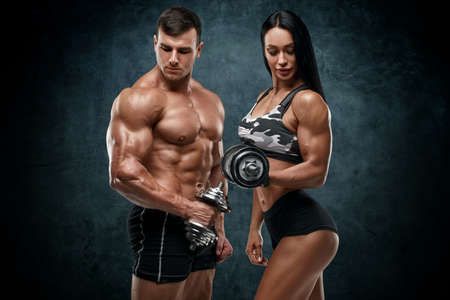 Sporty couple workout with dumbbells. Muscular man and woman showing muscles Stockfoto