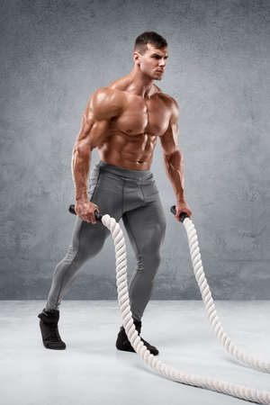 Muscular man working out with heavy ropes. Strong male naked torso abs