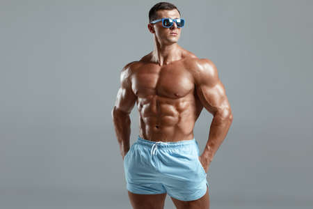 Muscular man naked torso abs, isolated on background. Fitness male model in fashionable sunglasses Stockfoto