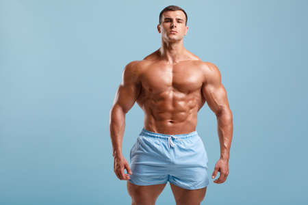 Handsome muscular man naked torso abs, isolated on blue background. Fitness male model