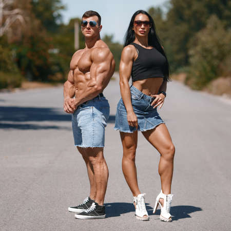 Muscular couple outdoors. Sporty man and woman showing muscles Stockfoto