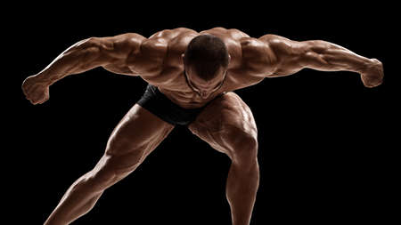Muscular man showing muscles, isolated on black background. Strong male with his arms stretched out Stockfoto