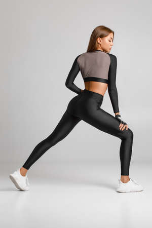 Sexy fitness woman. Beautiful athletic girl, isolated on the gray background