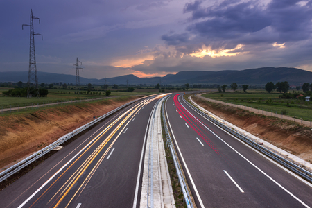 Highway, lines and car-trails leading in to dramatic sunset with colorful, fluffy clouds