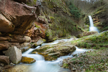 Colorful amphitheater of a mountain creek and a waterfall, during spring in a forest, photographed from a low angle perspective with blur motion water