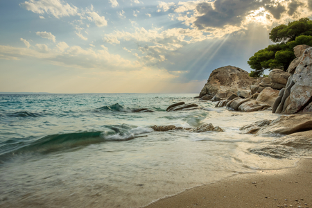 Sun rays passing through the clouds above amazing Koviou beach and beautiful rock structure with a pine tree on the top