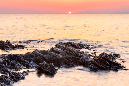 Sharp layers of eroded rocks in the reflective sea water and the setting sun on the horizon