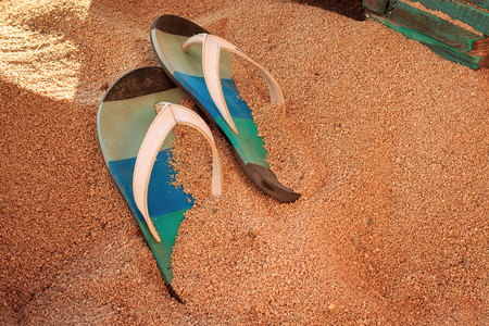 Colorful flip-flops on a golden, fine sand on a beach in a bar with wooden furniture Stock fotó
