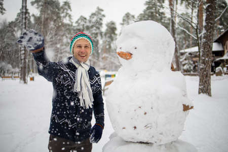 Man Cheerful Hipster Knitted Hat And Warm Gloves Play With Snowman Snow