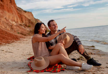 Romantic Happy Multi-Ethnic Couple Chinese Woman And Caucasian Man On Beach In Love At Sunset