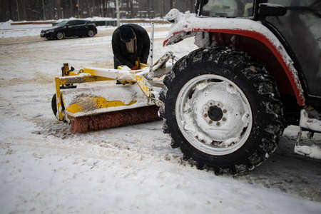 Tractor Cleans Snow With A Brush On The City Avenue.