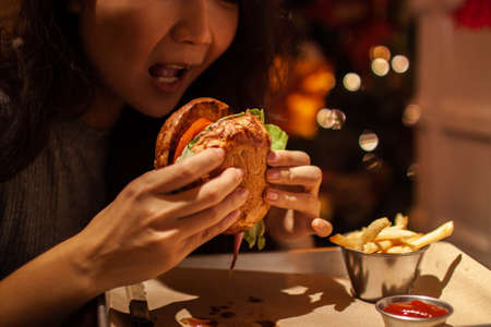 tasty burger with cheese and cutlet in hand