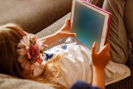 Girl using digital tablet on sofa at home.