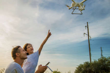 outdoor recreation Leisure for family. Birthday gift. A man and little girl launch a radio-controlled aircraft or a drone or a helicopter into the sky. Stock Photo