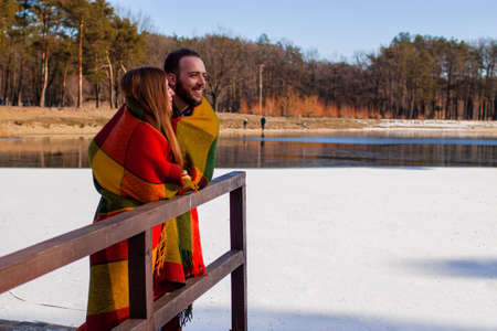 Couple in a winter forest and frozen lake. Young lovers in winter jackets laugh.