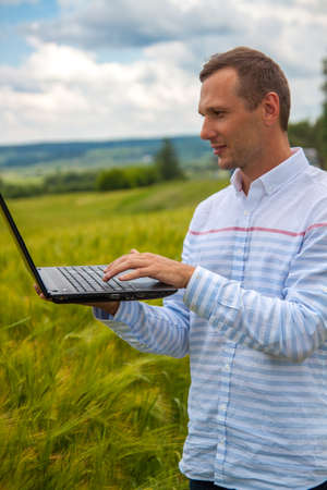 businessman with laptop and smartphone working in wheat field in blue sky background.