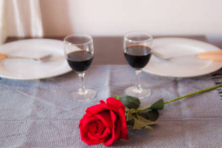 Couple Making A Toast At A Romantic Dinner On Restaurant Table With Red Rose.